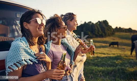 Cropped shot of friends having drinks while out in the countryside