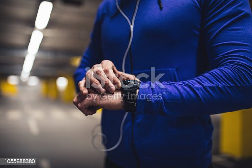 Shot of a young man setting the workout time on his smart watch.