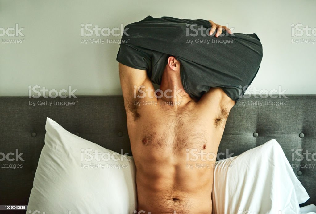 Getting comfy for bed Cropped shot of an unrecognizable man undressing on his bed at home Abdomen Stock Photo