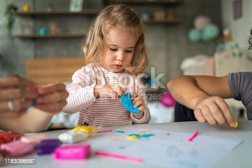 Cute toddler girl making shapes of plasticine modeling clay, unrecognizable people next to her