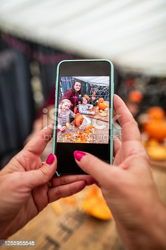 Personal perspective of a photo of a family at a pumpkin picking farm, being taken on a mobile phone. The family is sitting at a table carving pumpkins.