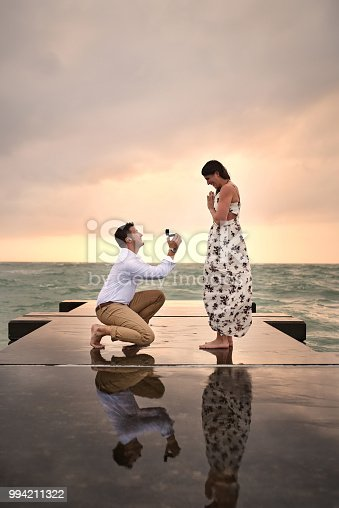 Full length shot of a handsome young man proposing to his girlfriend on the jetty at the beach