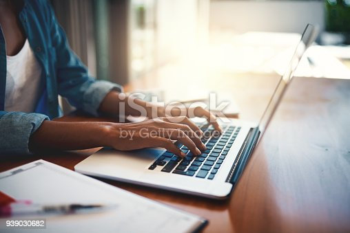 Closeup shot of an unrecognizable woman using a laptop while working from home