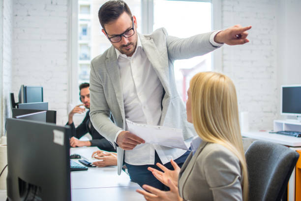 Getting fired. Angry boss pointing female employee on exit way. stock photo
