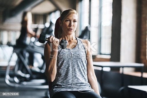 Shot of a mature woman lifting weights at the gym