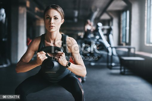 Cropped shot of an attractive young woman working out with a kettle bell in the gym
