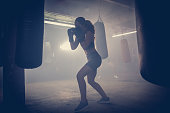 Young woman  boxer with dramatic lighting