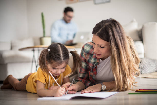 Getting help with my tasks. Getting help with my tasks. Little girl working her homework with mother. Focus is on foreground. parent stock pictures, royalty-free photos & images