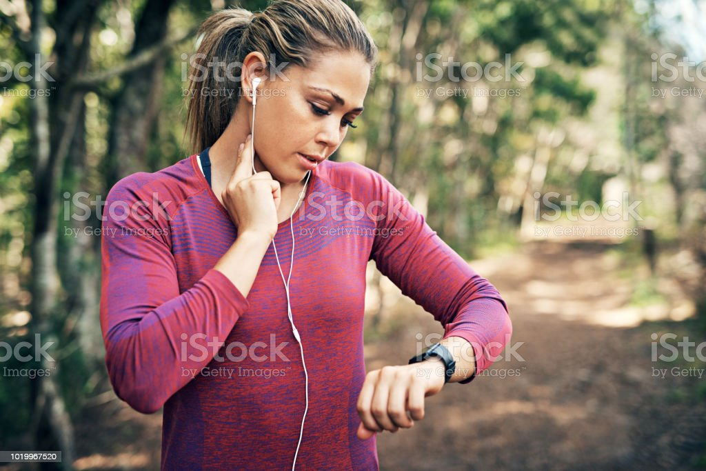 Getting her heart rate up Cropped shot of an attractive young female athlete tracking her pulse while out for a morning run 20-29 Years Stock Photo