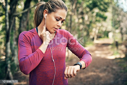 Cropped shot of an attractive young female athlete tracking her pulse while out for a morning run