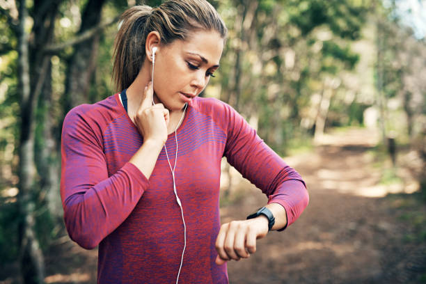 Getting her heart rate up Cropped shot of an attractive young female athlete tracking her pulse while out for a morning run woman taking pulse stock pictures, royalty-free photos & images