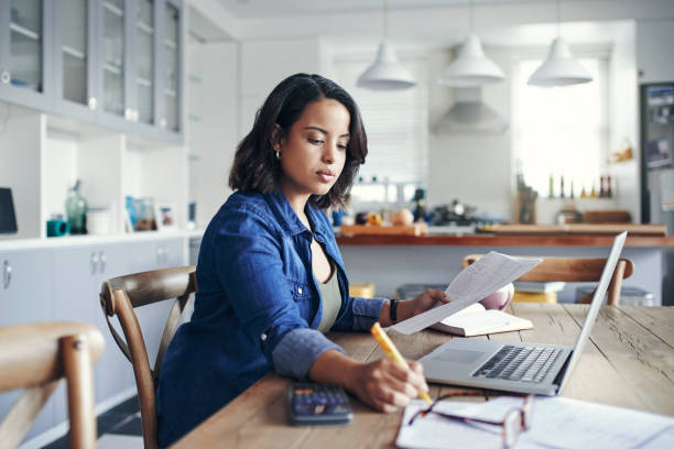 Getting her home business up and running Shot of a young woman using a laptop and  going through paperwork while working from home plan document stock pictures, royalty-free photos & images