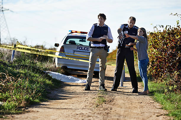 Getting her statement Shot of a woman showing police officers where she found the body at a crimescene police interview stock pictures, royalty-free photos & images