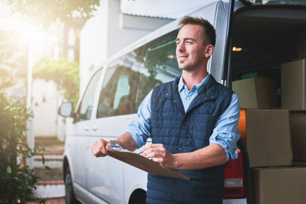 Getting his deliveries out Shot of a courier checking his deliveries in his van commercial land vehicle stock pictures, royalty-free photos & images