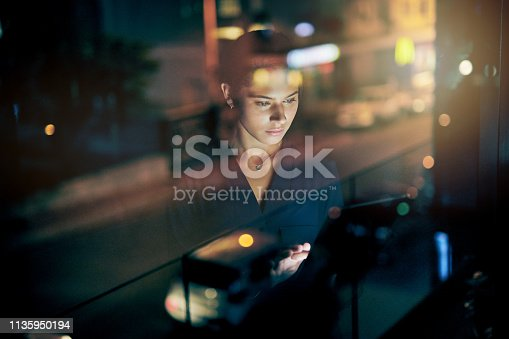Shot of a young businesswoman using a digital tablet during a late night in a modern office