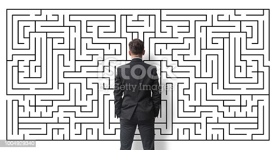 Businessman looking at a labyrinth on a white wall
