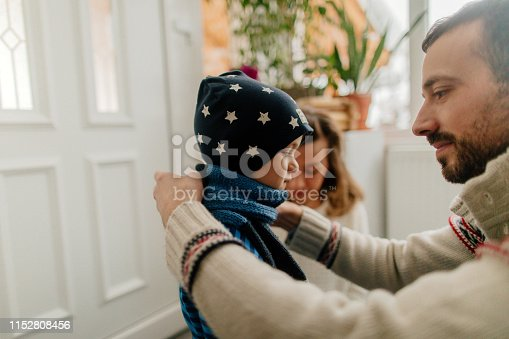 Photo of a young family putting some warm clothes on and getting ready for winter activities
