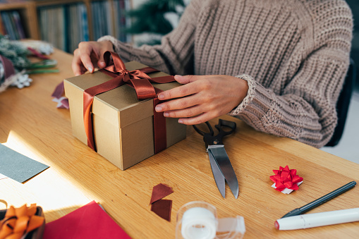 Smiling woman sitting at home and opening a Christmas/birthday present during a video call, adapting to the new normal concept.