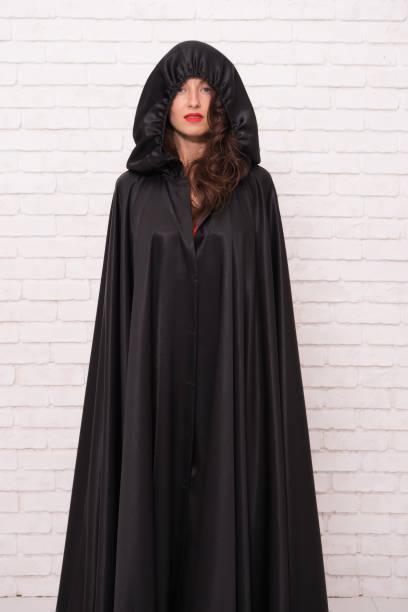 vorbereitung auf kostümparty. party-mädchen auf weißer ziegelwand. sinnliche frau trägt schwarze toga mit party-look. sexy mädchen als hexe für halloween-party gekleidet - toga kostüm stock-fotos und bilder