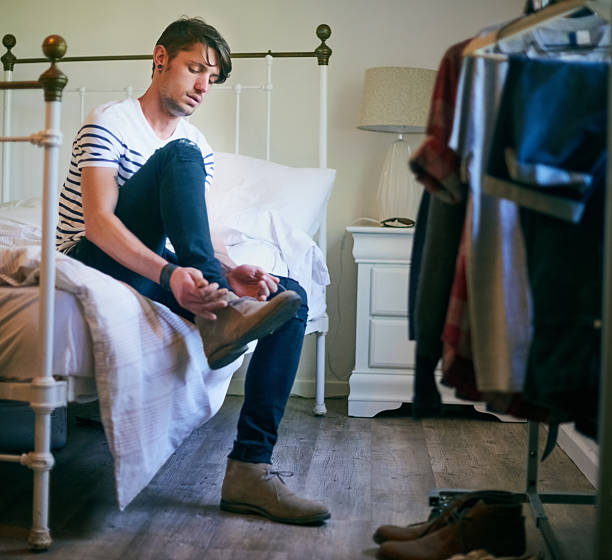 Getting ready for his day Shot of a handsome young man sitting on his bed lacing up his shoes skinny jeans stock pictures, royalty-free photos & images