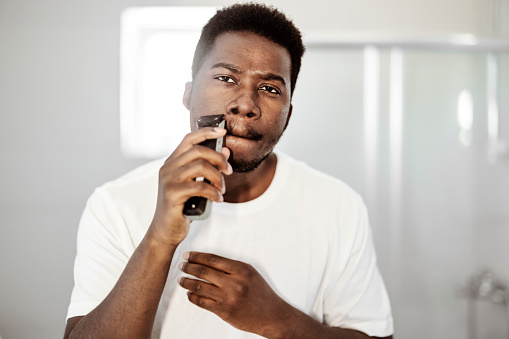 Portrait of young african american man shaving with trimmer