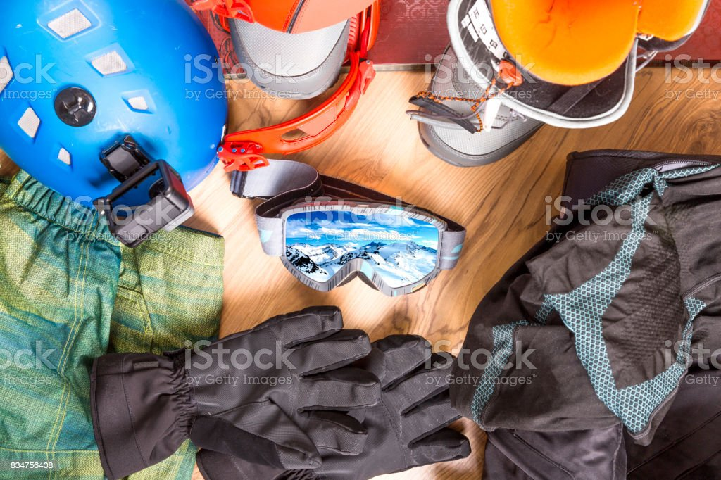 Getting ready for winter vacation. Set of snowboard equipment on the wooden floor. Goggles, snowboard, jacket, boots, gloves, suitcase stock photo