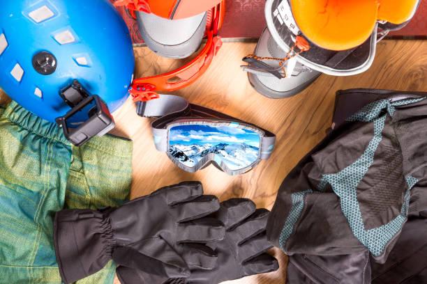 preparándose para las vacaciones de invierno. conjunto de equipos de snowboard sobre el suelo de madera. gafas snowboard, chaqueta, botas, guantes, maleta - set deportivo fotografías e imágenes de stock