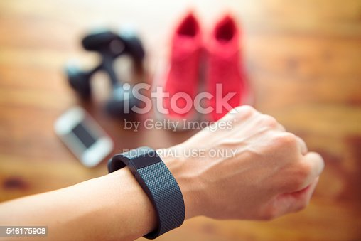 Berlin, Germany - July 11, 2016: Woman getting ready for her workout wearing a FITBIT as an activity tracker to control her heartrate.