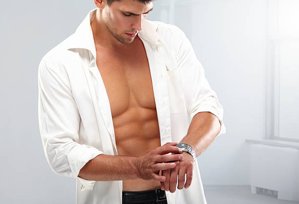 Getting ready. Muscular man in unbuttoned white shirt looking at his wristwatch. fully unbuttoned stock pictures, royalty-free photos & images