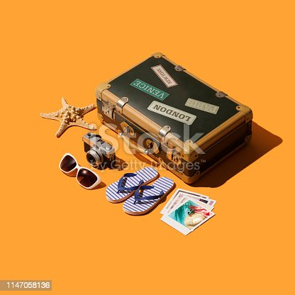 Getting ready to leave for summer vacations on the beach: vintage suitcase and isometric travel accessories