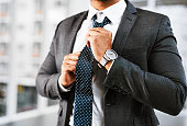 Closeup shot of a businessman adjusting his tie in an office