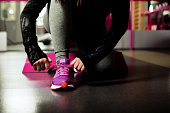 A woman tying the laces on her snickers, getting ready for the gym