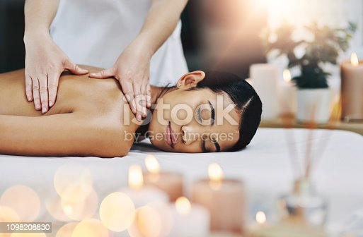 Shot of a relaxed an cheerful young woman getting a massage indoors at a spa