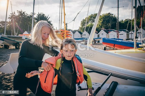 Little girl receiving a helping hand from her grandmother to get her lifejacket on.