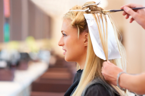 Pretty young woman having her hair highlighted at the salon