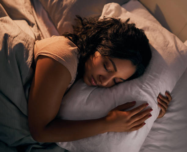 Getting some much needed sleep High angle shot of a beautiful young woman sleeping in her bed at home during the night face down stock pictures, royalty-free photos & images