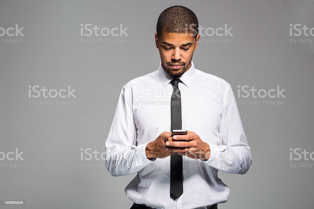 Getting some news Cropped shot of a handsome young businessman using a cellphone. 2015 Stock Photo