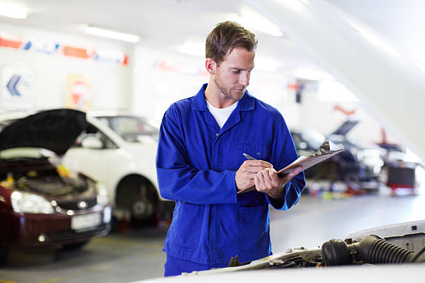 Getting started on a service A handsome mechanic holding a clipboard and performing checks on a cars engine bonnet stock pictures, royalty-free photos & images