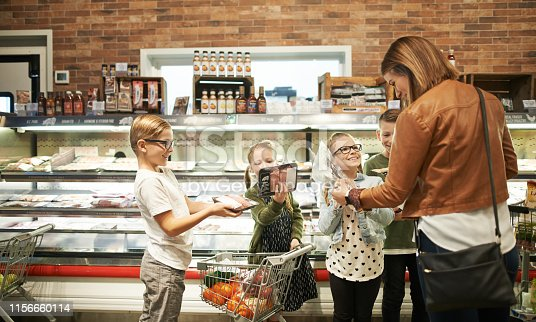 Shot of adorable young kids shopping with their mother at a grocery store