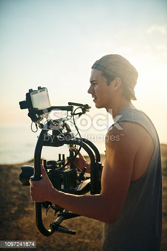 Shot of a focused young man shooting a scene with a state of the art video camera outside on a beach during the day