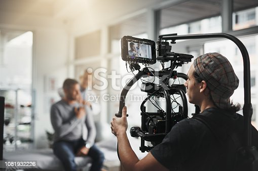 Behind the scenes shot of a camera operator shooting a scene with a state of the art camera inside of a studio during the day