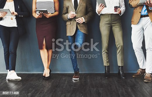 Cropped studio shot of a group of businesspeople using wireless technology while waiting in line against a gray background