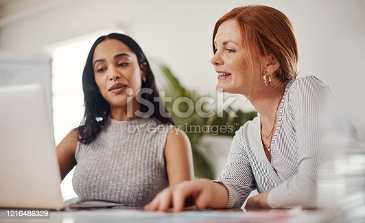 Shot of two businesswomen working together on a laptop in an office