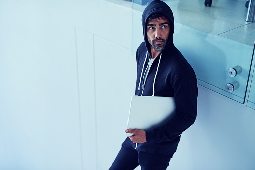 Shot of a shady-looking young man holding a laptop in an office