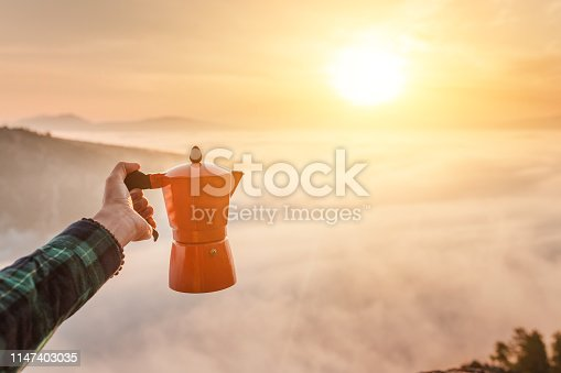 Geyser aluminium coffee maker on the background of fog and mountians