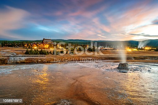 Stock photograph of a geyser cone and the landmark Old Faithful Inn in the Upper Geyser Basin, Yellowstone National Park on a cloudy, colorful evening