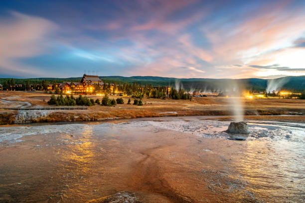Geyser and Old Faithful Inn in Yellowstone National Park Stock photograph of a geyser cone and the landmark Old Faithful Inn in the Upper Geyser Basin, Yellowstone National Park on a cloudy, colorful evening inn stock pictures, royalty-free photos & images
