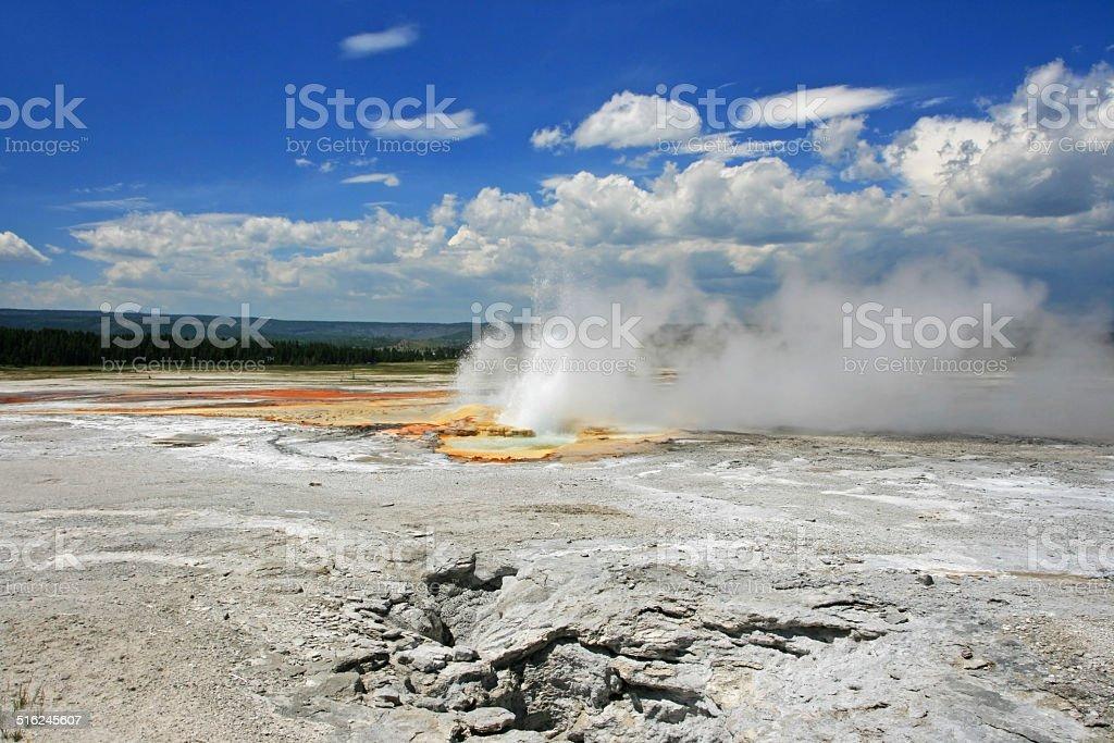 Geyser Basin erupts against blue sky stock photo