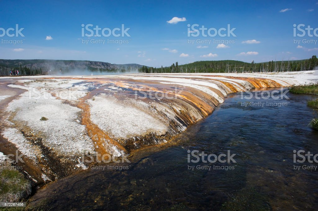 Geyser steam rising beside river in Yellowstone stock photo