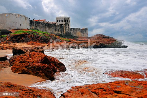 Cape Coast, Ghana: Cape Coast castle, the ocean and red rocks, used by several European nations to buy slaves from their African partners for delivery to clients in the Americas - Slave castle and the waves of the Atlantic ocean - colonial architecture - photo by M.Torres